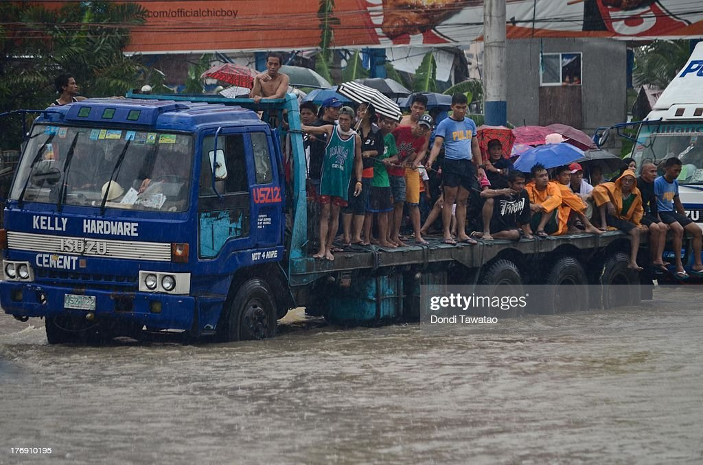 Affected residents are ferried to higher ground by police rescue teams after floodwaters inundated parts of Las Pinas on August 19, 2013 in Las Pinas City south of Manila, Philippines. Tropical storm Trami which was enhanced by monsoon rains swept overnight through the southern metropolitan cities of Manila and leaving huge parts of four provinces underwater forcing residents to evacuate their homes and seek shelter in evacuation centers. At least three fatalities were recorded with thousands more still needing to be rescued.