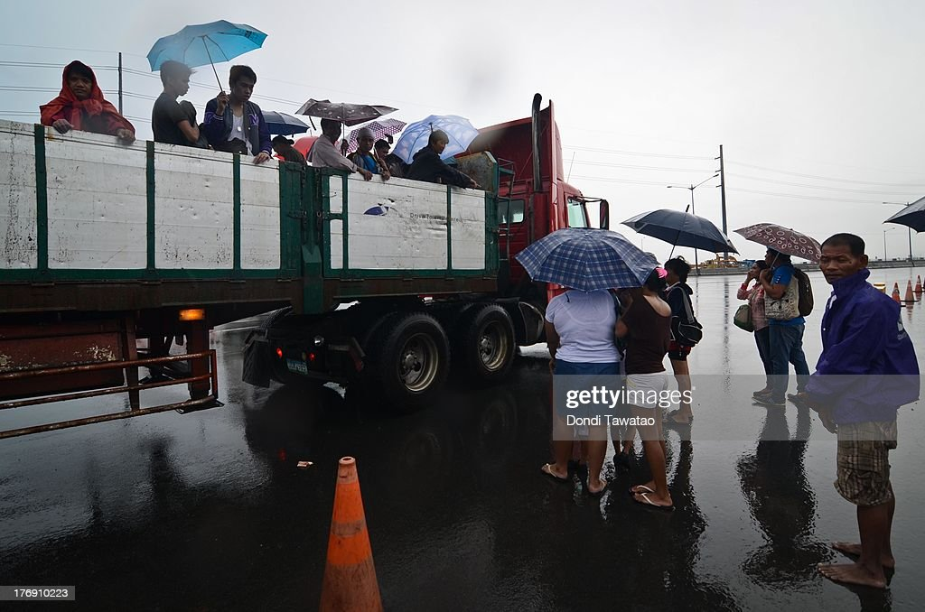 Affected residents hitch a ride in a ten wheeler truck during a downpour that inundated parts of Las Pinas on August 19, 2013 in Las Pinas City south of Manila, Philippines. Tropical storm Trami which was enhanced by monsoon rains swept overnight through the southern metropolitan cities of Manila and leaving huge parts of four provinces flooded forcing residents to evacuate their homes and seek shelter in evacuation centers. At least three fatalities were recorded with thousands more still needing to be rescued.