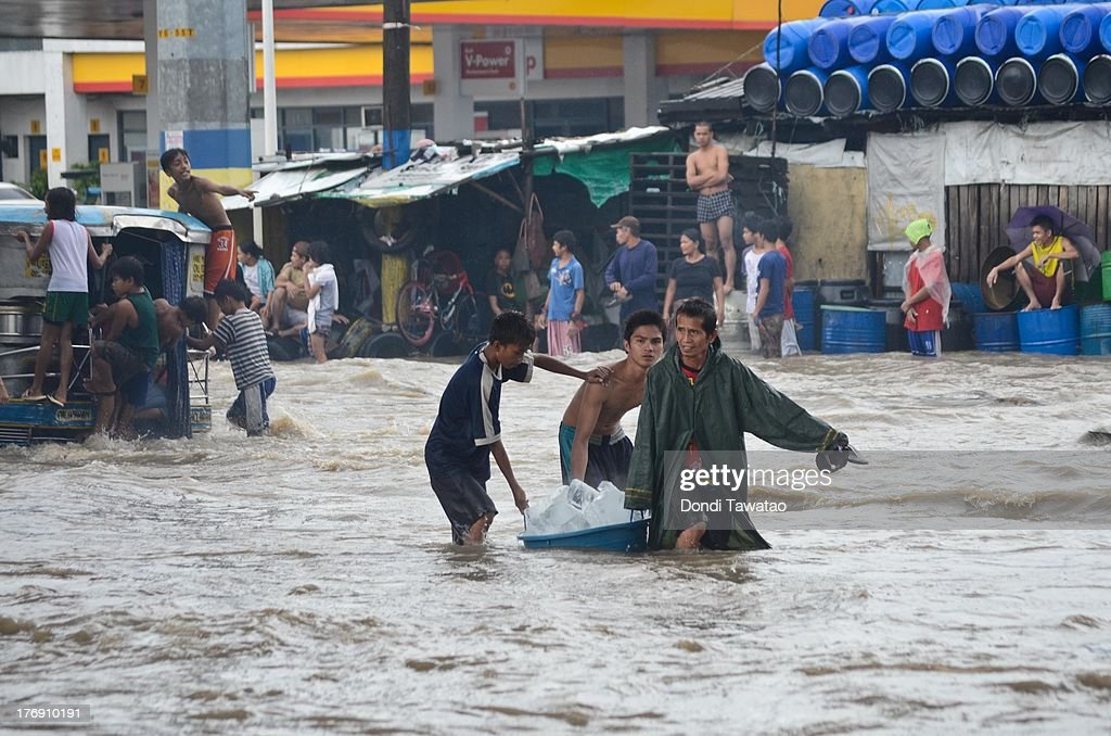 Affected residents wade through floodwaters that inundated parts of Las Pinas on August 19, 2013 in Las Pinas City south of Manila, Philippines. Tropical storm Trami which was enhanced by monsoon rains swept overnight through the southern metropolitan cities of Manila and leaving huge parts of four provinces underwater forcing residents to evacuate their homes and seek shelter in evacuation centers. At least three fatalities were recorded with thousands more still needing to be rescued.