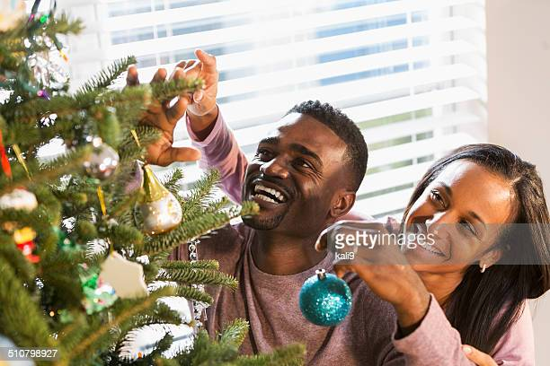 Affectionate African American couple decorating Christmas tree together