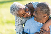 Close up of an affectionate senior African American couple outdoors.  The man is sitting, looking over his shoulder into his wife's smiling face.  She is standing behind him, bending down with her arm