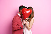 Affectionate couple covering face with balloon and kissing