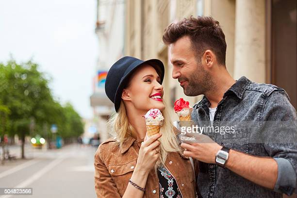 Affectionate couple eating ice cream in the city