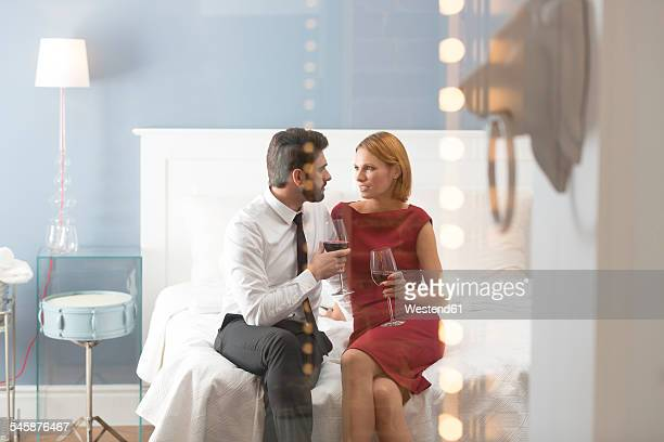 Affectionate couple holding wine glasses in bedroom