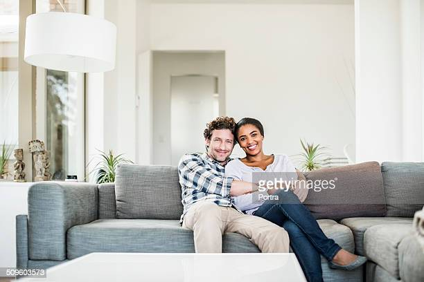 Affectionate couple relaxing on sofa at home