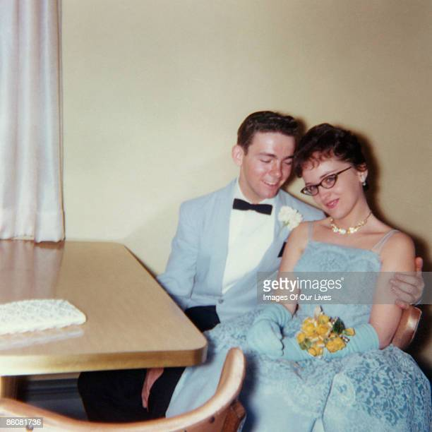 Affectionate couple sitting at table at prom
