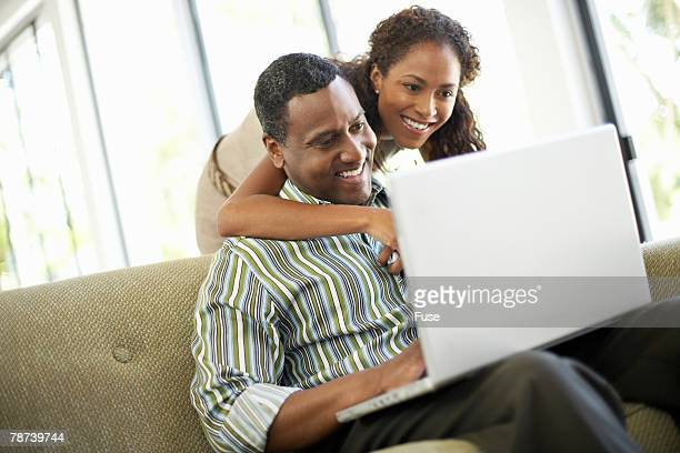 Affectionate Couple Using Laptop in Living Room