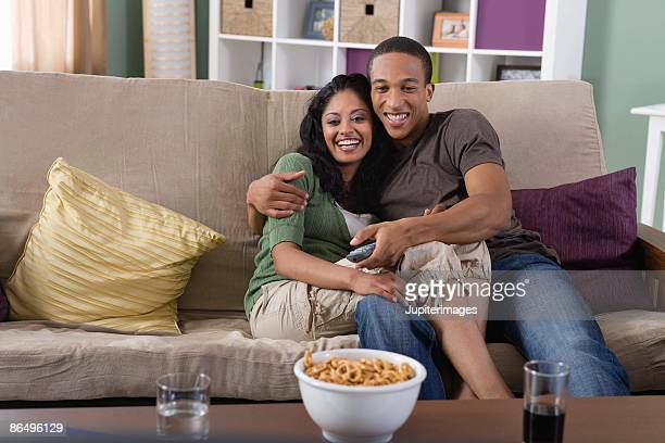 Affectionate couple watching TV at home