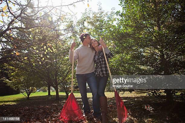 Affectueux couple avec Le ratissage des feuilles