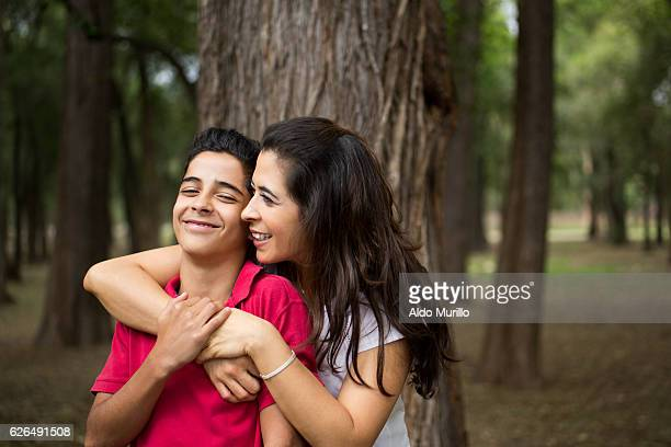 Affectionate latin mother embracing teen son and smiling