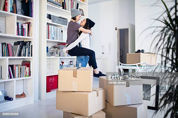Affectionate lesbian couple by stacked cardboard boxes