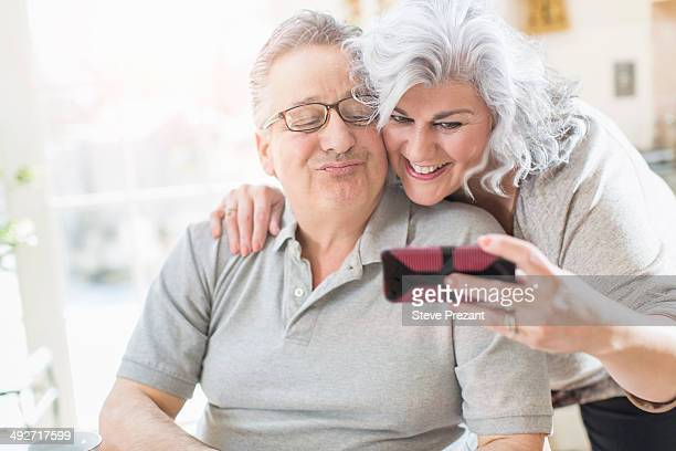 Affectionate mature adult couple taking a self portrait at home