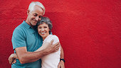 Portrait of affectionate mature couple embracing each other against red background and smiling. Senior couple against red wall with copy space.