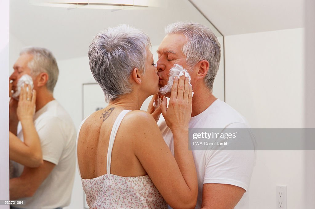 affectionate mature couple kissing in bathroom stock photo
