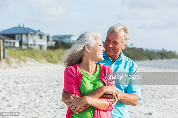 Affectionate mature couple standing on beach