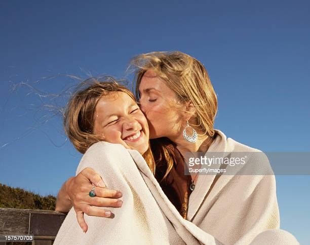 Affectionate Mom and Teen Daughter Wrapped in Blanket