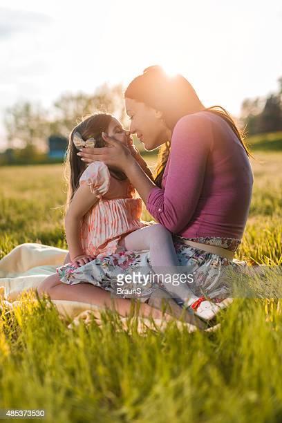 Zärtlich Mutter und Tochter küssen im Freien mit Ihrer Nase.