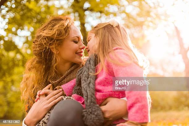 Zärtlich Mutter und Tochter küssen mit Ihrer Nase im Freien.