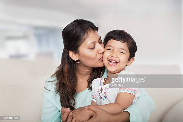 Affectionate mother holding and kissing her daughter on the couch
