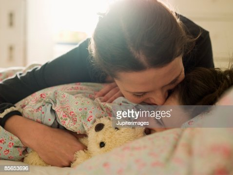 Affectionate mother with daughter in bed