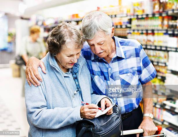 Affectionate senior couple check shopping list in supermarket