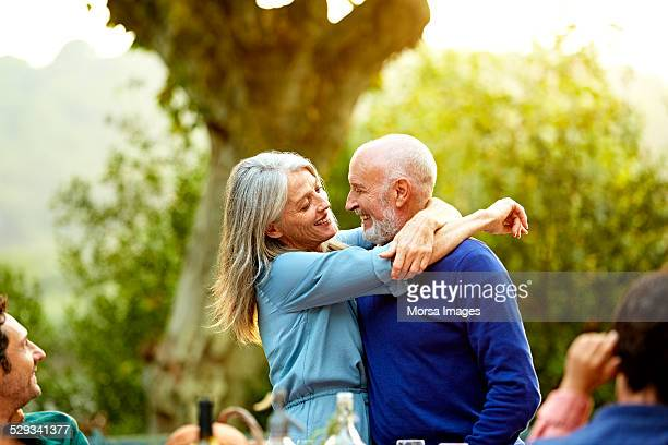 Affectionate senior couple embracing in yard
