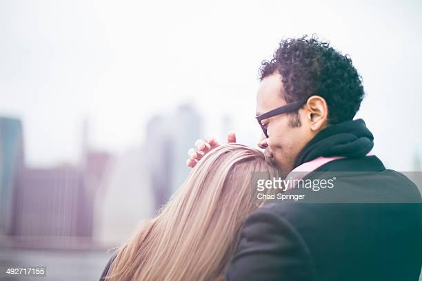 Affectionate young couple and Manhattan skyline, New York, USA