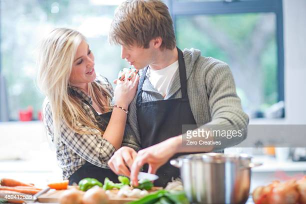 Affectionate young couple preparing food