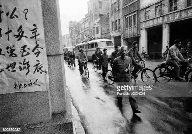 Affichette et cyclistes dans une rue de Canton en février 1979 en Chine