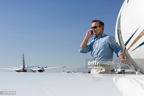 Affluent Travel-Man Talking on Cell Phone by Airplane