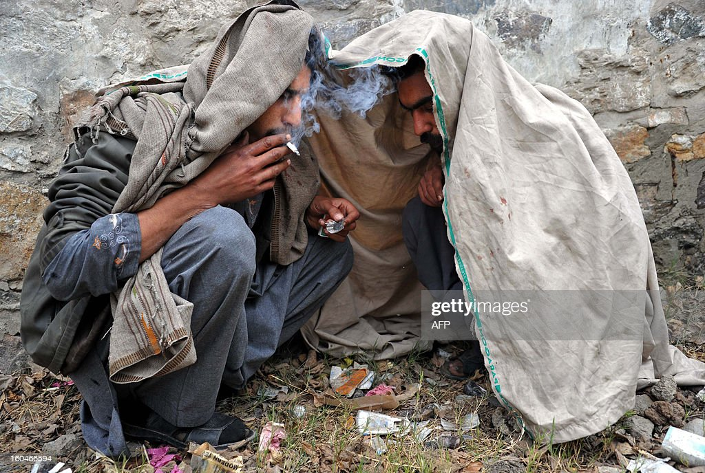 Afghan addicts smoke heroin in Jalalabad on January 31, 2013. Eleven years after the 2001 U.S.-led invasion to drive the Taliban from power, Afghanistan produces 90 percent of the world's illegal opium, funding much of the militia's insurgency despite an expensive Western eradication program. AFP PHOTO/Noorullah Shirzada
