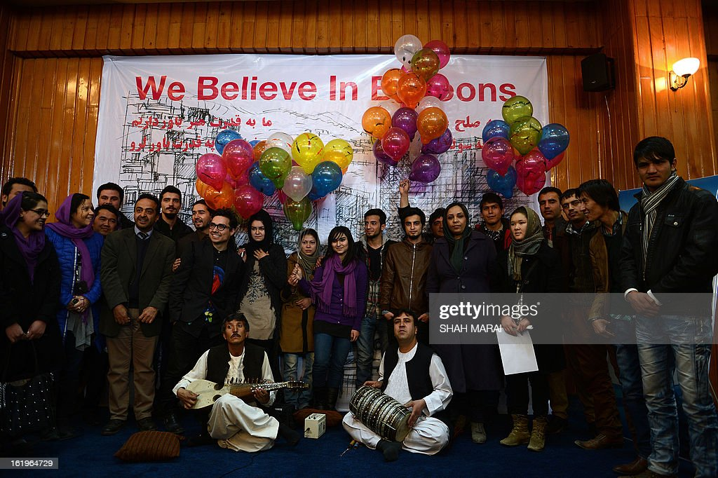 Afghan and foreign volunteers for 'We Believe In Balloons' pose for a picture in Kabul on February 18, 2013. Despite grinding poverty and more than three decades of war, a New York-based artist believes 10,000 pink balloons can help bring peace and happiness to Afghans on the streets of Kabul. Yazmany Arboleda has already unleashed coloured balloons in India, Japan and Kenya. He hopes that Afghanistan can be the next to benefit from 'simple happiness' despite being in the grip of an 11-year Taliban insurgency.