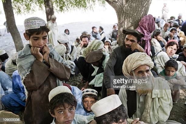 Afghan and Pakistani refugees wait to be registered by the Afghan Head of Disaster Management Committee and to receive an aid distribution on August...