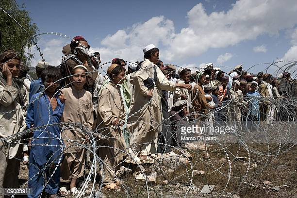 Afghan and Pakistani refugees wait to receive humanitarian assistance by the Afghan Head of Disaster Management Committee during an aid distribution...