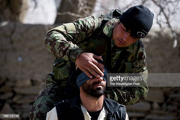 Afghan Army soldier blindfold a local suspect after one of the Afghan soldiers had just been shot by a Taliban fighter while searching a compound the...