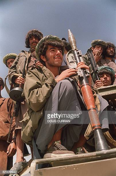 Afghan army soldiers loyal to the JamiateIslami faction of Ahmed Shah Massood patrol atop an APC in JabalOsSaraj 24 April 1992 about 65 kilometers...