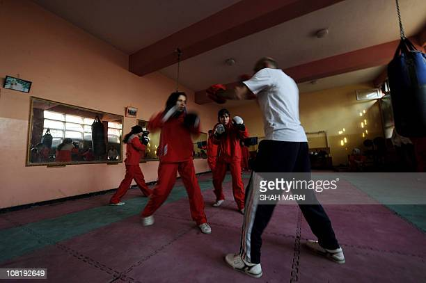 Afghan boxing coach Saber Sharifi trains girls as they participate in a boxing training session in a training room at the Kabul stadium in Kabul on...