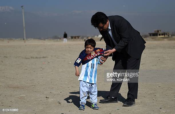 Afghan boy fiveyearold Murtaza Ahmadi a young Lionel Messi fan has his shirt adjusted by his uncle Yasin Ahmadi as he plays football wearing a...