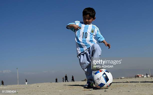 TOPSHOT Afghan boy fiveyearold Murtaza Ahmadi a young Lionel Messi fan plays football as he wears a donated and signed shirt by Messi on a field in...
