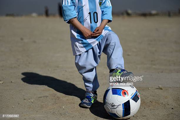 Afghan boy fiveyearold Murtaza Ahmadi a young Lionel Messi fan poses wearing a donated and signed shirt by Messi on a field in Kabul on February 26...