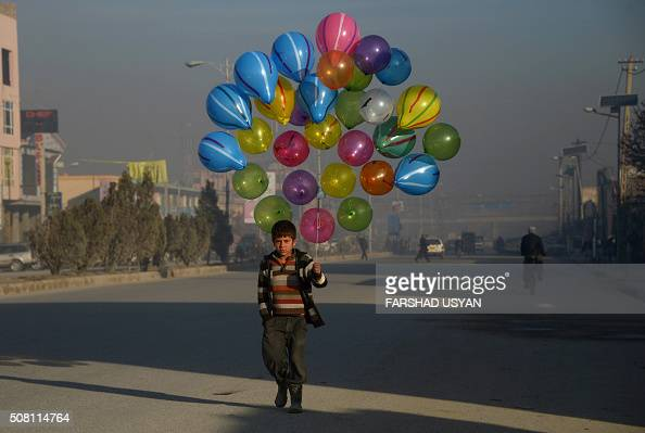 TOPSHOT Afghan boy Hizbullah walks as he looks for customers to buy his balloons on the streets of MazariSharif on February 3 2016 AFP PHOTO /...
