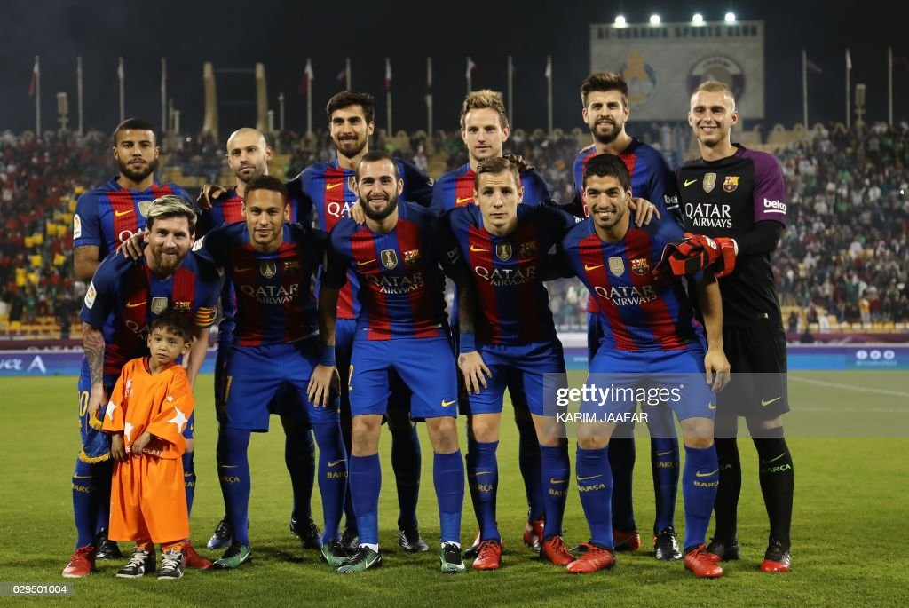 TOPSHOT - Afghan boy Murtaza Ahmadi poses for a picture with the FC Barcelona team: (top L to R) Rafinha, Javier Mascherano, André Gomes, Ivan Rakitic, Gerard Piqué, Ter Stegen (bottom L to R) Lionel Messi, Neymar Junior, Paco Alcácer, Lucas Digne, Luis Suárez , on the pitch before the start of a friendly football match against Saudi Arabia's Al-Ahli FC on December 13, 2016 in the Qatari capital Doha. Barcelona play Saudi champions Al-Ahli in a friendly in Doha, the Spanish club's last major obligation of its four year shirt sponsorship deal with Qatar Airways. JAAFAR