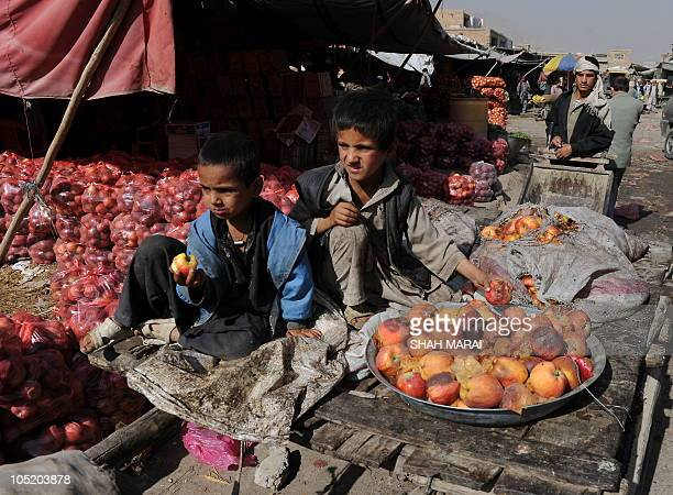 Afghan boys collect rotten apples at the vegetable market in Kabul on October 12 2010 Afghanistan is one of the world's poorest countries where...