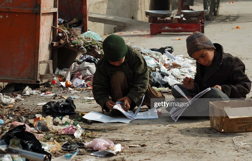 Afghan boys look through books found in the garbage in Kandahar on January 31, 2013. AFP PHOTO/ Mamoon Durrani