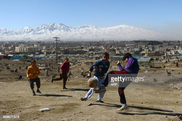 Afghan boys play football at a cemetery in Kabul on February 16 2014 The Afghan national team is popularly known as the Lions of Khurusan and is...