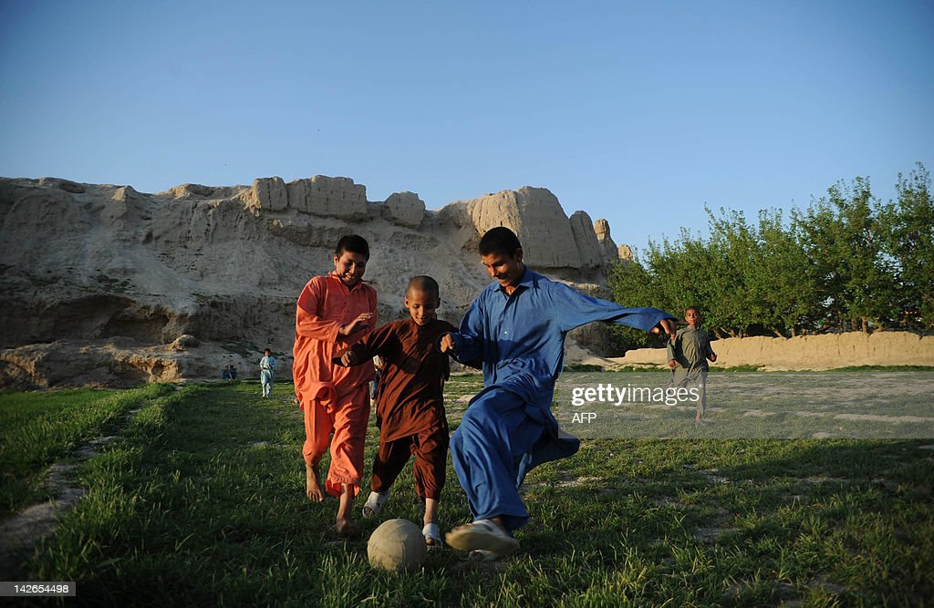 Afghan boys play football on the outskirts of Mazari Sharif capital of Balkh province on April 10 2012 Mazari Sharif the capital of Balkh province is...