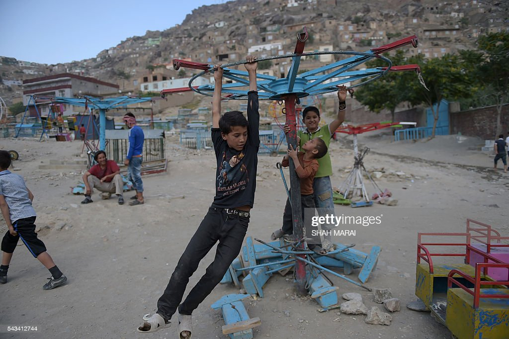 Afghan boys play on a swing prior to Iftar, the time to break fast during the Islamic month of Ramadan, in Kabul on June 28, 2016. Throughout the month, devout Muslims must abstain from food, drink and sex from dawn until sunset when they break the fast with the Iftar meal. / AFP / SHAH
