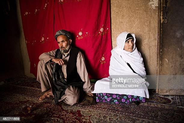 Afghan breast cancer patient Bassira sits next to her husband Habibollah at her sister's house in the northwestern city of Herat on April 2 2014...