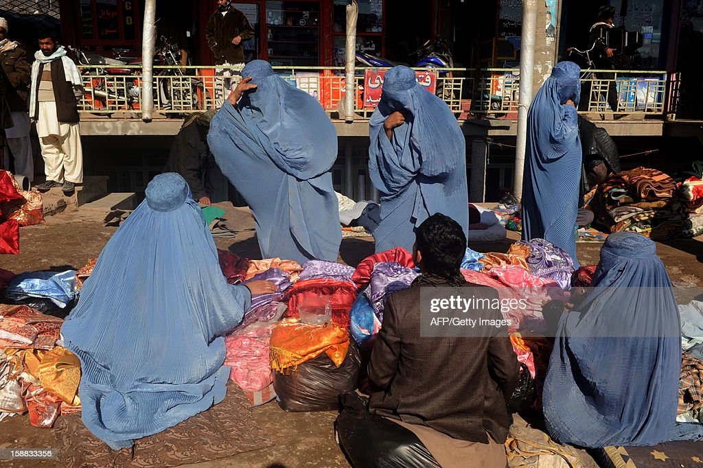 Afghan Burqa clad women shop in a street in Herat on December 31, 2012. Over a third of Afghans are living in abject poverty, as those in power are more concerned about addressing their vested interests rather than the basic needs of the population, a UN report said. AFP PHOTO/ Aref Karimi