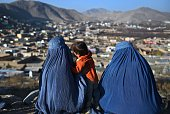 Afghan burqa clad women sit in a cemetery overlooking the outskirts of Kabul on December 1 2015 AFP PHOTO / Wakil Kohsar / AFP / WAKIL KOHSAR